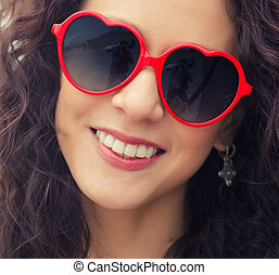 Smiling woman in heart shape glasses