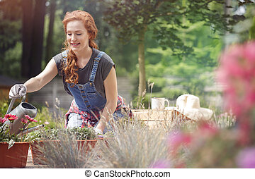 Smiling woman in jean dungarees and gloves on hands watering...