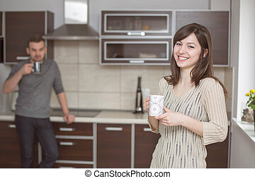Smiling woman in kitchen with blurred man