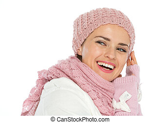Smiling woman in knit winter clothes looking back on copy space