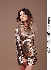 Smiling woman in luxurious glitter dress.