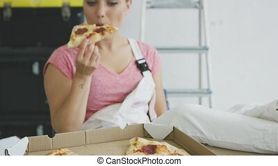 Smiling woman in overalls eating tasty pizza - View of...