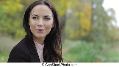 Smiling woman in park - Attractive woman in black jacket and...