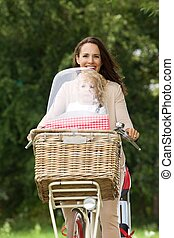 Smiling woman in park on bike