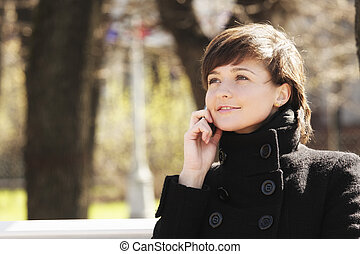 Smiling woman in park with cellphone