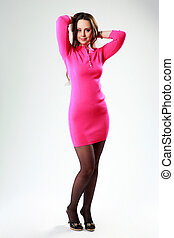 Smiling woman in pink dress standing on gray background