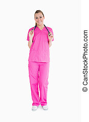 Smiling woman in pink scrubs - Smiling woman standing in ...