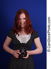 smiling woman in polka dot dress with old TLR camera