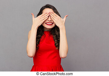 Smiling woman in red dress covering her eyes