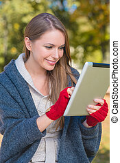 Smiling woman in red mittens using a tablet