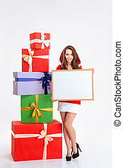 Smiling woman in santa claus cloth holding blank board