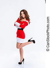 Smiling woman in santa claus cloth standing with arms folded