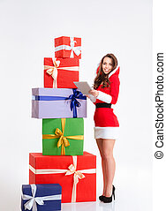 Smiling woman in santa claus cloth using tablet compter