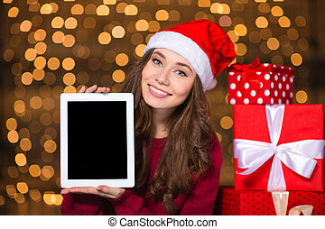 Smiling woman in santa claus hat holding tablet blank screen