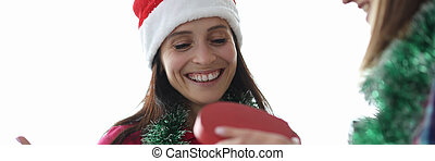 Smiling woman in santa claus hat looks at gift box