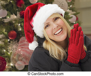 Smiling Woman in Santa Hat In Front of Christmas Tree