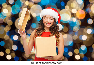 smiling woman in santa hat opening christmas gift -...
