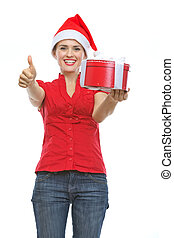 Smiling woman in Santa hat with Christmas present box showing thumbs up