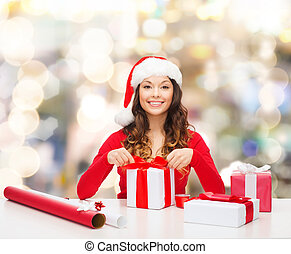 christmas, holidays, celebration, decoration and people concept - smiling woman in santa helper hat with decorating paper packing gift boxes over lights background