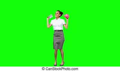 Smiling woman in slow motion holding a piggy bank