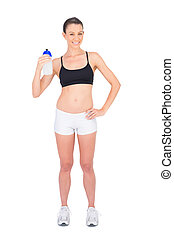 Smiling woman in sportswear holding flask