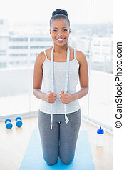 Smiling woman in sportswear holding measuring tape around her neck while sitting on exercise mat
