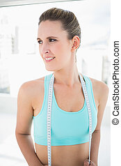 Smiling woman in sportswear holding measuring tape