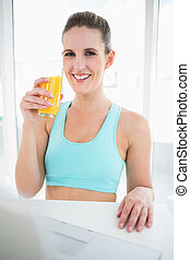 Smiling woman in sportswear holding orange juice