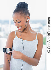 Smiling woman in sportswear listening to music and using her music player in bright room at home