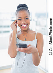 Smiling woman in sportswear listening to music while looking at camera in bright room