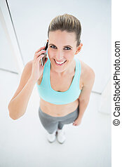 Smiling woman in sportswear talking on the phone