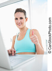 Smiling woman in sportswear using laptop giving thumbs up