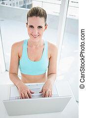 Smiling woman in sportswear using laptop