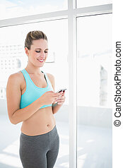 Smiling woman in sportswear using phone