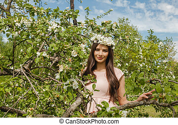 Smiling woman in spring flowers garden outdoors. Beautiful fashion model girl on blue sky, green leaves and apple tree flowers background outdoor