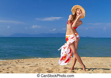 Smiling woman in straw hat on sandy beach