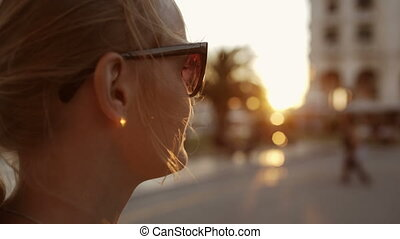 Smiling woman in sunglasses outdoor during sunset