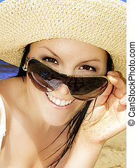 smiling woman in sunhat on the beach