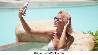 Smiling woman in swimwear taking selfie on smartphone ...