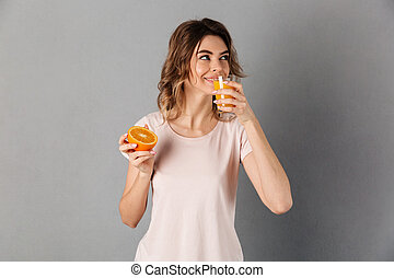 Smiling woman in t-shirt holding orange and drinking juice
