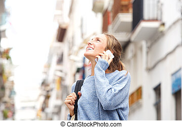 Smiling woman in the city talking on cellphone
