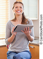 Smiling woman in the kitchen with tablet