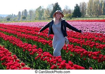 Smiling woman in tulip fields.