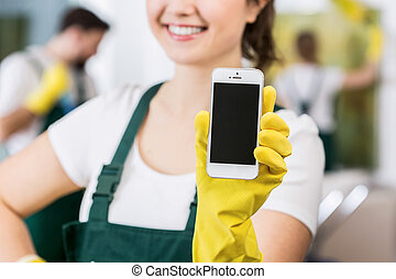 Smiling woman in uniform holding cellphone
