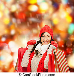 smiling woman in warm clothers with shopping bags - retail ...
