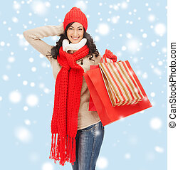 smiling woman in warm clothes with shopping bags - retail ...