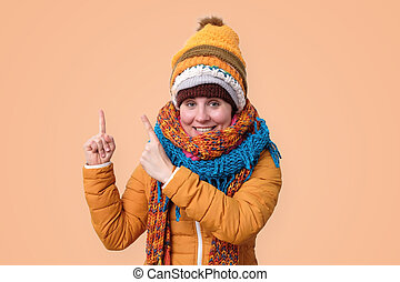 Smiling woman in warm winter clothes scarf and hat pointing up