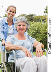 Smiling woman in wheelchair with her daughter
