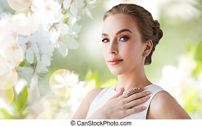 smiling woman in white dress with diamond jewelry