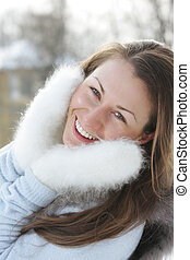 Smiling woman in white mittens